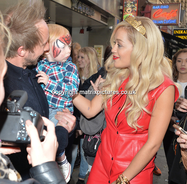 NON EXCLUSIVE PICTURE: PALACE LEE / MATRIXPICTURES.CO.UK<br /> PLEASE CREDIT ALL USES<br /> <br /> WORLD RIGHTS<br /> <br /> British singer and actress Rita Ora is pictured leaving the studios of London's Capital FM Radio Station.<br /> <br /> The 23 year old Black Widow singer wears a brightly coloured red leather-look dress paired with a red jacket, Louboutin heels and a gold crown on her head.<br /> <br /> Before getting into her waiting car, Rita stops to meet her fans, sign autographs and pose for pictures.<br /> <br /> MAY 11th 2014<br /> <br /> REF: LTN 142252