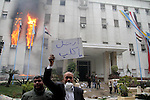 "Egyptian protesters stand in front of burning building during a anti-government protesters demonstrate against president Hosni Mubarak regime in Alexandria, Egypt, Jan. 28, 2011. Egyptian President Hosni Mubarak defied a quarter-million protesters demanding he step down immediately, announcing he would serve out the last months of his term and ""die on Egyptian soil."" He promises not to seek re-election, but that does not calm public fury as clashes erupt between his opponents and supporters. Photo by Ahmed Ramadan"