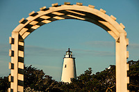 A wooden archway attractively frames the Ocracoke Lighthouse near Silver Lake Harbor off Pamlico Sound on Ocracoke Island. Ocracoke Light remains among the oldest lighthouses still active on the southern coast of North Carolina's Outer Banks, and it is the second oldest operating lighthouse in the United States (the first is Sandy Hook Light house in New Jersey). The first Ocracoke Lighthouse was built in 1803 on Shell Castle Island inside the Ocracoke Inlet not far from Blackbeard's hideout. Destroyed by lightning in 1818 it was replaced by the current light in 1823 on the banks of the inlet near Ocracoke Village. The white-brick conical lighthouse stands 75 feet tall and has 220 stairs to its top, though visitors are not allowed to climb. Ocracoke Island can only be reached by ferry. Charlotte NC photographer Patrick Schneider has extensive photo collections of the following lighthouses: Bodie Island Lighthouse, Bald Head Island Lighthouse, Cape Fear Lighthouse, Cape Hatteras Lighthouse, Cape Lookout Lighthouse, Currituck Beach Lighthouse, Diamond Shoal Lighthouse, Federal Point Lighthouse, Oak Island Lighthouse, and Ocracoke Lighthouse on Ocracoke Island.