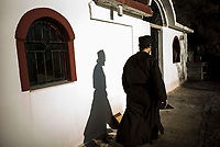 Mount Athos - The Holy Mountain.<br /> Father Iusif walks past his church that he built where his cell once stood before it was burnt down in a fire in 2004.  <br /> <br /> Photographer: Rick Findler
