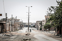 A Syrian woman walks among the ruins of the Al Atarib town. The city was flattened during months of shelling by the Syrian army, turning the city of 30,000 inhabitants into a ghost town of only 300, as the army was trying to sweep out the rebels. Today, Al Atarib belong to the FSA controlled territory, but it still being watched by the Syrian army and bombed occasionally.