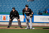 Charlotte Knights first baseman Zack Collins (8) holds Brandon Nimmo on as umpire Brian Peterson looks on during an International League game against the Syracuse Mets on June 11, 2019 at NBT Bank Stadium in Syracuse, New York.  Syracuse defeated Charlotte 15-8.  (Mike Janes/Four Seam Images)
