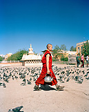 MONGOLIA, Ulaanbaatar, young monk walking with a pot of tea at the Gandan Monastery