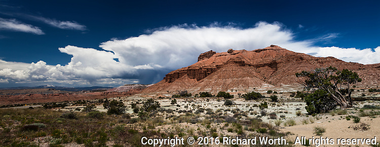 Panoramic view of red cliffs under blue sky with white clouds at San Rafael Swell along Interstate 70 in Utah.
