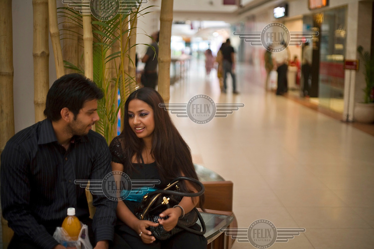 A couple talk on a bench at the Select Citywalk shopping centre, New Delhi.