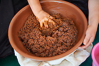 Argan paste being mixed by hand prior to pressing out the oil. Cooperative Marjana, Ounara, Essouira, Morocco