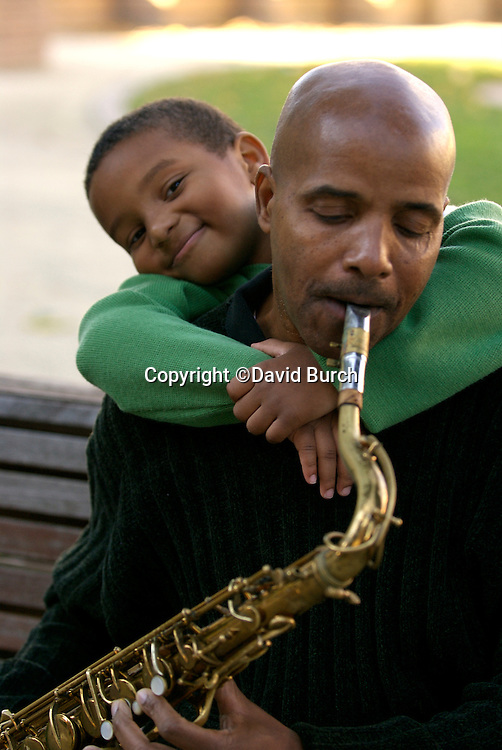 African American man playing saxophone for his grandson
