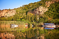 Boats on Dalyan Çay? River with Lycian Rock Tombs in the cliffs . Mediterranean coast Turkey