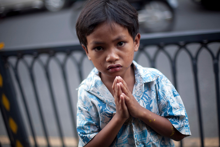 A young boy begs to tourists in Phnom Penh, Cambodia. <br /> <br /> Photos &copy; Dennis Drenner 2013.