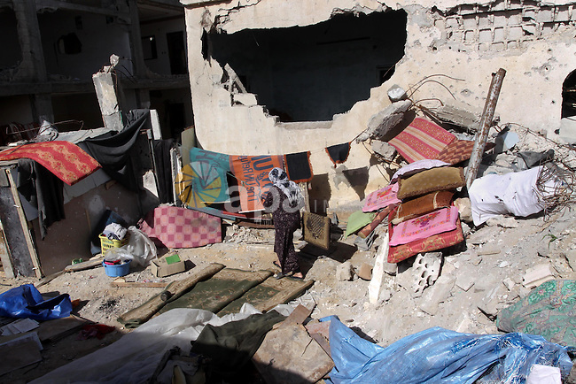 A Palestinian woman works on the rubbles of her destroyed house during a protest against the United Nations decision to suspend payments for Palestinians, whose houses were damaged during a 50-day war last summer, in Beit Hanoun in the northern Gaza Strip January 30, 2015. The main U.N. aid agency in the Gaza Strip said on Tuesday a lack of international funding had forced it to suspend payments to tens of thousands of Palestinians for repairs to homes damaged in last summer's war. Photo by Mohammed Asad