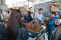 "Customers shop at Grandaisy Bakery at the New Amsterdam Market on South Street in New York during the market's opening day for the season, Sunday, April 29, 2012. The market, located in the former Fulton Fish Market, features vendors who source their artisanal food directly from local farmers and stands of the farmers'  themselves . For opening day they promoted their ""Bread Pavilion"" which had booths from 16 local artisanal bakeries. (© Richard B. Levine)"