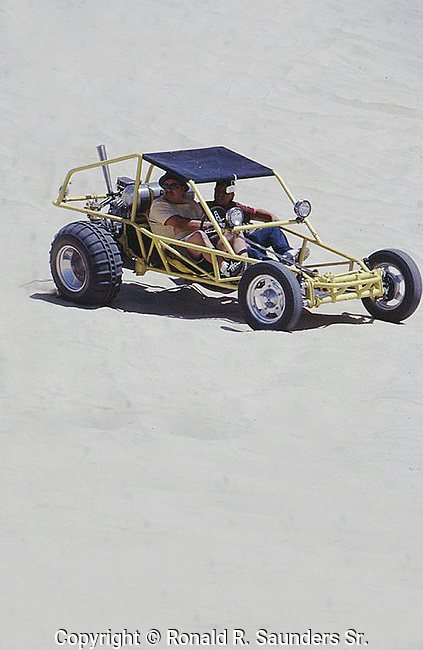 TWO MEN WATCH TOURIST IN ATV'S ON SAND DUNES