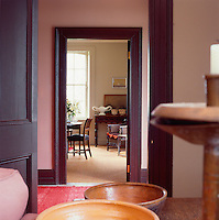 A view from the sitting room to the living room, the dark painted doors add definition and drama.