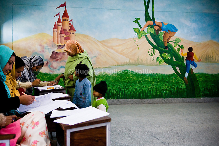 Une femme se prépare à voter accompagnée de ses enfants dans l'école qui sert de bureau de vote. Hommes et femmes votent séparément.