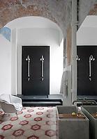 Dans l'aile remaniée d'un ancien couvent d'Anacapri, le jeune architecte napolitain Giuliano dell'Uva a aménagé une maison d'hôtes dont les murs historiques et la simplicité du décor très contemporain se mêlent à l'esprit estival des années 1970. -- Des voûtes plusieurs fois centenaires, des carreaux en ciment début XXe, la mémoire du lieu se confronte à la modernité radicale. Douche deux places en résine gris anthracite et robinetterie Zazzeri, blocs lavabos en marbre veiné de Giuliano dell'Uva. Touche glamour années 1950 : fauteuil, Galerie Nabis à Capri.