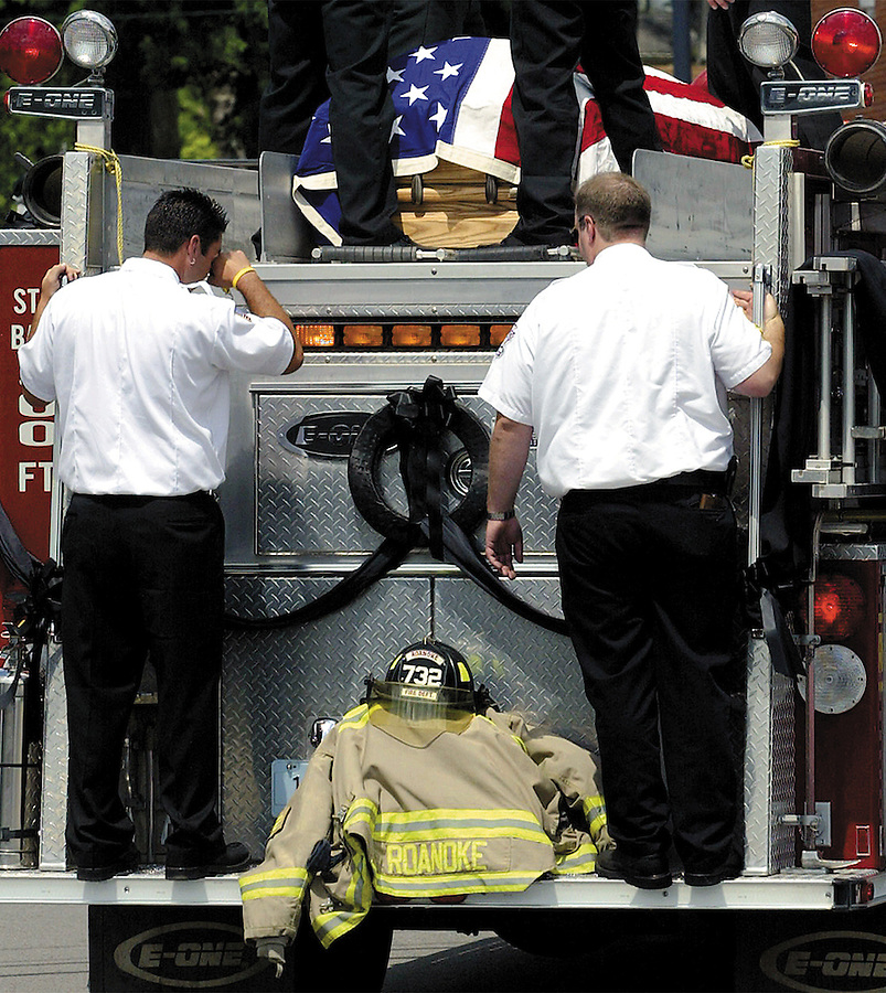By Andrew Hancock&amp;#xA;A firefighter (lower left) wipes his eye as Roanoke Firefighters ride their truck through the intersection of 2nd and Main Street in Roanoke with the Wilbert L. &quot;Junior&quot; Hile's casket atop the firetruck after picking up his gear (Helmet, fire suit and boots) from the fire station . Members of all Huntington County volunteer fire departments were represented at the funeral, and a procession of at least one truck from each department in honor of Junior, drove from the funeral home, past the fire department and stopped as the last truck, a Roanoke truck with Junior's casket, stopped to get his gear and proceed to Saint Josephs Catholic Church in Roanoke for Juniors last call.<br />