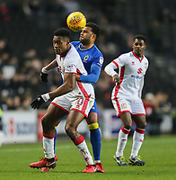 Chuks Aneke of MK Dons shields the ball from Tom Soares of AFC Wimbledon (2nd left) during the Sky Bet League 1 match between MK Dons and AFC Wimbledon at stadium:mk, Milton Keynes, England on 13 January 2018. Photo by David Horn.