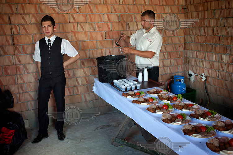 Two men employed by a catering company prepare food and drink for a wedding party inside a house which is under construction in the village of Tarsolt. .