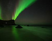 Northern Lights - Aurora borealis shine in sky over Myrland beach, Flakstadøy, Lofoten Islands, Norway