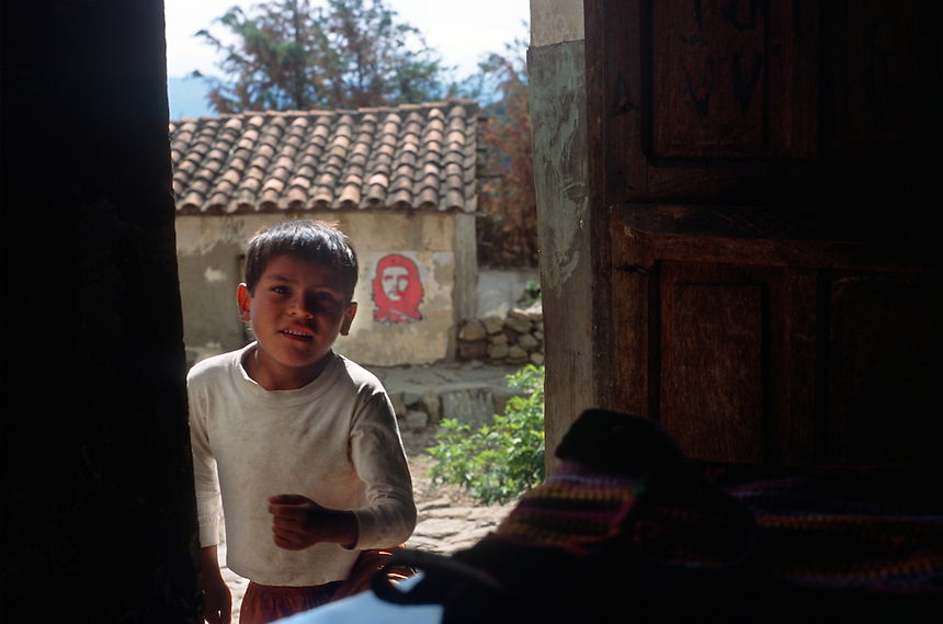 """A young boy ducks through a doorway in front of one of many examples of Ernesto """"Che"""" Guevara grafitti in La Higuera, Bolivia, Saturday, Nov. 13, 2004. Guevara was captured by the Bolivian army in 1967 in a nearby valley and executed in La Higuera days later. Guevara and fellow communist guerillas were attempting to launch a continent-wide revolution modeled on Guevara's success in Cuba in the late 1950s. The Bolivian government recently began promoting the area where he fought, was captured, killed and burried for 30 years as the """"Ruta del Che,"""" or Che's Route. (Kevin Moloney for the New York Times)"""