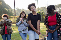 From left: Freshmen Hailey Jarman, 15 (CQ), Jessica Ballesteros, 14, (CQ) Jayla Wilkins, 14, (CQ) and Quataysia Dixon, 14, (CQ) participate in a group exercise that requires them to close close their eyes during a Peer Group Connection field day where freshmen students meet their senior mentors at Greene Central Central High School in Snow Hill, NC Friday, September 22, 2017. (Justin Cook for Education Week)