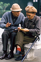 A peacful morning in Chiang Kai-Shek Memorial Park is the setting for this discussion between these two friends. They represent an honored Generation - the elderly are highly esteemed in Taiwan. two elderly men. Taipei, Taiwan central city park.