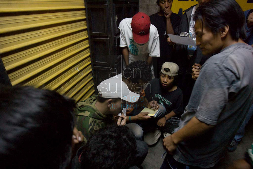 "Guatemalan youth hang out on a corner in Zone 8 of Guatemala City, Guatemala on Monday night, June 13, 2005 as Doctors Without Borders workers gather their names. Many of ""los niños de la calle,""--the children of the streets--are addicted to paint thinner, soaking balls of cloth with it and holding the toxic rags to their mouths. The children and young adults prefer solvent to glue because it is cheaper and helps them forget their hunger pains and cold. Carlos Toledo, director and founder of Nuestros Derechos--Our Rights- a Guatemalan non-governmental organization that tries to help the children off the streets and into society, said there are about 10,000 children living without homes or stable lives in Guatemala. ""These children are illegal in their own country,"" Toledo said, since most have no legal documentation and are not recognized as existing by the government."