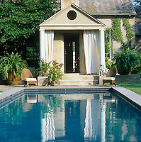 A temple-fronted pavilion was built as a folly next to the lap pool with a putty-coloured stucco facade to match the interior walls of the house