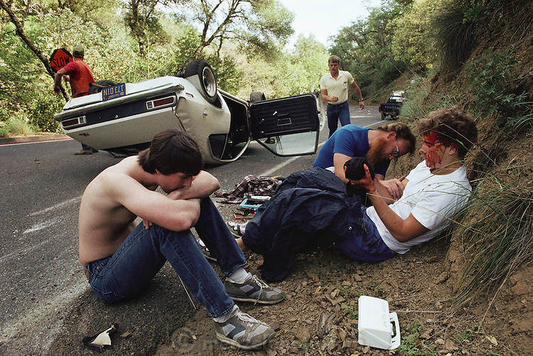 Passerbys attending to the wounds of a car accident victim on the roadside of Highway 121, Napa County, California. USA