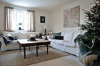 Long white sofas with practical loose covers structure one end of the spacious living area which adjoins the dining room