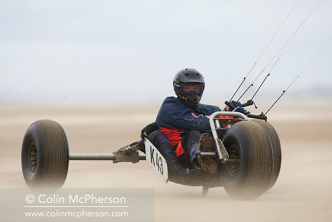 Tommy Grierson  of England taking part in one of the races at the European Kite Buggy Championships at Hoylake, Wirral, north west England. Around 75 buggies, with both male and female pilots, from 10 countries took part in the annual event which lasted from 5-9 September 2011. The three-wheeled, single-seated, steel frame buggy was powered  by a traction, or power kite and could achieve speeds of up to 70mph/110km/h.
