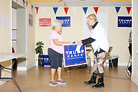 """Claribel Biba-Ferrer, 76, of Hialeah, (left) picks up campaign signs and stickers from Blanca Vrotsos, 62, of Doral, Florida, at the Donald Trump campaign office in Hialeah, Miami, Florida, on Sun., Oct. 9, 2016. Wearing a """"Women For Trump"""" shirt, Vrotsos has been volunteering almost everyday for 10 months at the Donald Trump campaign office in Hialeah, Miami, Florida. She helps recruit volunteers, register people to vote, and train other volunteers. Originally from Cuba, she has been a US citizen for 15 years and says she is """"extremely Republican."""" She first voted in 2000 and voted for George W. Bush. She says she will always support the Republican nominee for president."""