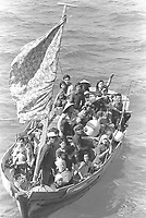 1984 file photo - 35 Vietnamese refugees wait to be taken aboard the amphibious command ship USS BLUE RIDGE (LCC-19).  They are being rescued from a 35 foot fishing boat 350 miles northeast of Cam Ranh Bay, Vietnam, after spending eight days at sea.