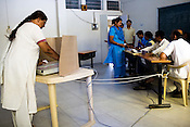 A voter is seen casting her vote on the electronic polling machine in a polling booth in a school in Sterling City, Ahmedabad, Gujarat India. About 49 per cent of the 3.65 crore electorate today exercised their franchise in the single phase polling in the state's 26 Lok Sabha constituencies on April 30th 2009.