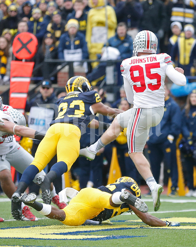 Ohio State Buckeyes punter Cameron Johnston (95) is roughed up by Michigan Wolverines safety Jordan Glasgow (23) at Michigan Stadium on November 28, 2015. (Chris Russell/Dispatch Photo)at Michigan Stadium on November 28, 2015. (Chris Russell/Dispatch Photo)