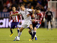 Chicago Fire forward and captain Brian McBride (w) battles with rookie midfielder Ben Zemanski of Chivas USA. The Chicago Fire defeated CD Chivas USA 3-1 at Home Depot Center stadium in Carson, California on Saturday October 23, 2010.