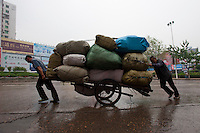 Daytime landscape view of a two men pulling a hand cart loaded with burlap bags on Hui Long Jie in Lóngmǎtán Qū of the Lúzhōu Prefecture City in Sichuan Province.  © LAN