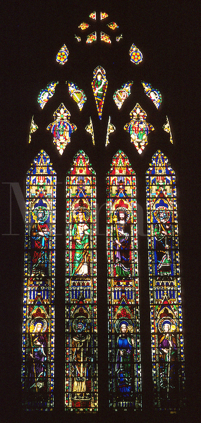 late afternoon sun highlights stained glass window, churches, religions, Christianity, art, interior. Ely England United Kingdom Great Britain.