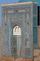 "Detail of portal of Mausoleum of the middle group, (""Nameless 1"" Mausoleum), 1380s, Shah-I Zindah ensemble, and in the distance the blue cupola of the Bibi-Khanym Madrasah and mausoleum, Samarkand, Uzbekistan, pictured on July 19, 2010, at dawn. The Shah-i-Zinda Complex is a necropolis of mausoleums whose legendary origin dates back to 676 when Kussam-ibn-Abbas arrived to convert the locals to Islam. So successful was he that he was assassinated whilst at prayer. His grave remains the centre of the sacred site which grew over many centuries, especially the 14th and 15th, into an architecturally stunning  example of ceramic art. The Mausoleum of the middle group.(""Nameless 1"" Mausoleum) was created by Usto Alim Nesefi, and is decorated  with relief painted majolica. The portal decorations are notable for the symbol of ""octagonal stars"". Samarkand, a city on the Silk Road, founded as Afrosiab in the 7th century BC, is a meeting point for the world's cultures. Its most important development was in the Timurid period, 14th to 15th centuries. Picture by Manuel Cohen."
