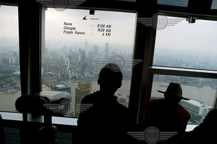 People looking out towards skyscrapers sprouting in downtown Shanghai from the 88th floor observation deck of the Jin Mao Tower, China's tallest building, situated in the Pudong district.