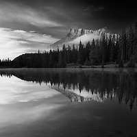Perfect Reflection of Mount rundle in the early morning. Symmetrical reflection, blue sky and trees. Black and White, square format