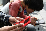 """May 9, 2010 - Tokyo, Japan - Young Japanese boys play Nintendo's portable video game 'DS' in front of the official Pokemon store in Tokyo on May 9, 2010. Nintendo recently announced that the DS handheld device had become the best selling gaming handheld of all time, with a total of 129 million units sold. The DS 'family' have surpassed the """"Game Boy"""" series which hit 118 million over two decades."""