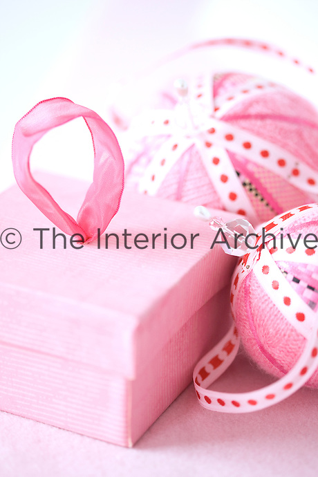 A close up of pink Christmas baubles and a small box