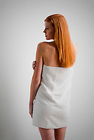 Young red haired woman wrapped in a towel, rear view