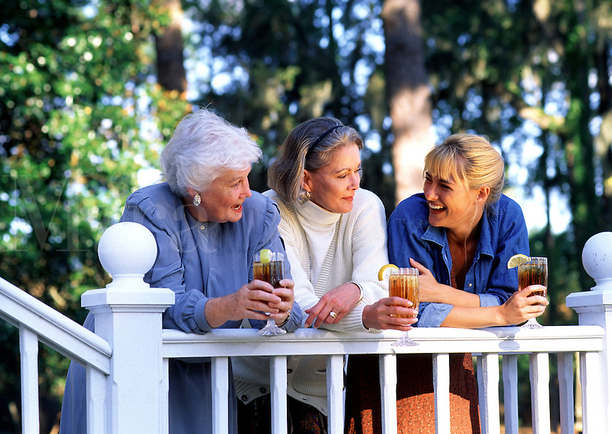 Three generations of women talking and drinking iced tea.