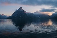 Osltind mountain peak reflects in fjord in soft summer twilight, Reine, Lofoten Islands, Norway