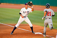 Joey Gallo #15 of the USA 18u National Team fields a throw as Michael Lorenzen #21 (Cal State Fullerton) of the USA Baseball Collegiate National Team hustles towards first base at the USA Baseball National Training Center on July 2, 2011 in Cary, North Carolina.  The College National Team defeated the 18u team 8-1.  Brian Westerholt / Four Seam Images