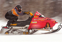A SNOWMOBILER RACES IN A HILL CLIMB EVENT AT MARQUETTE MOUNTAIN SKI HILL IN MARQUETTE MICHIGAN.