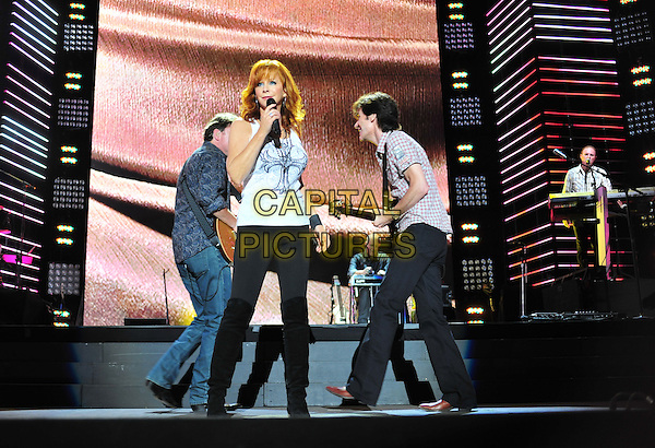 REBA McENTIRE .2010 CMA Music Festival Nightly Concert held at LP Field,  Nashville, Tennessee, USA, 11th June 2010..country music live on stage concert gig.full length Black leggings knee high boots white top  microphone singing .CAP/ADM/LF.©Laura Farr/AdMedia/Capital Pictures.