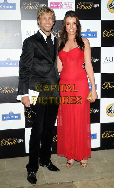 RICK PARFITT JR. & GUEST .Attending The Grand Prix Ball at The Hurlingham Club, London, England, .UK, 7th July 2010. .full length black suit tie red dress long maxi gold clutch bag .CAP/CAN.©Can Nguyen/Capital Pictures.